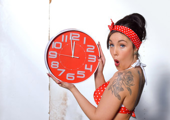 A young woman dresses up as a pin-up girl. She wears a polka dot vintage bathing suit.  Standing in front of an old white wall she holds a  red clock and shows off  facial expressions  in  the camera.