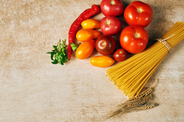 dry pasta and tomatoes on wooden background.Ingredients for pasta