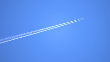 Engine exhaust contrails forming behind flying commercial airplane