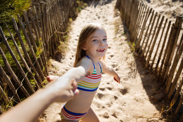 Smiling little girl holding her mother's hand on a sandy path