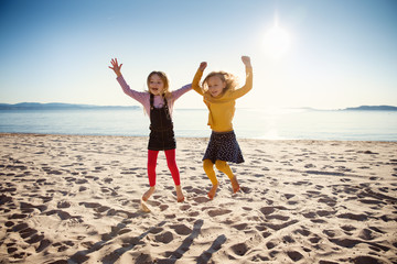 Two little girls jumping on a sandy beach