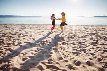 Two girls dancing on a sandy beach