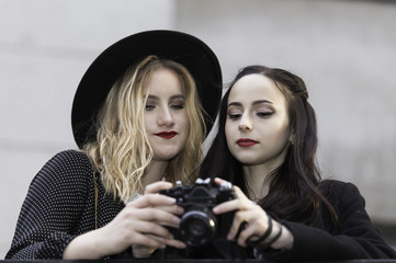 Two girls holding photo camera, wearing black clothes looking down to check the photo shoots. Outdoors