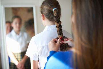 Over shoulder view of mother plaiting teenage schoolgirl daughter's hair