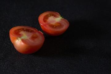 Halved tomato on black background