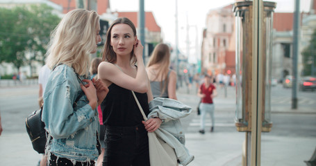 Two beautiful girls looking at clothes in a shop window. Teenage girls shopping together in a city.