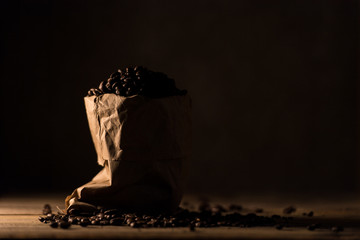 Coffee beans in paper bag against dark background.