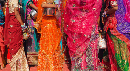 Beautiful crowd of colorfu women dressed traditional indian sari with patterns going for water with jars