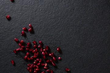 Pomegranate seeds on black background