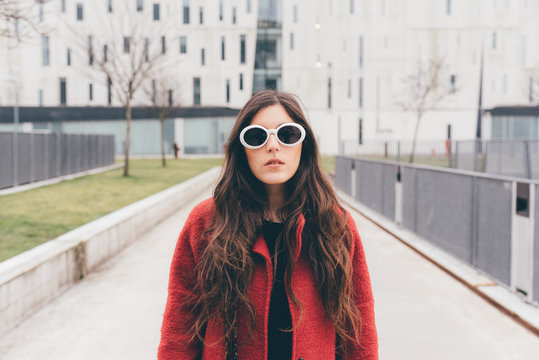 Portrait of young woman, wearing sunglasses, standing in urban environment
