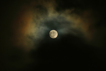 Full Moon on the Dark Sky with Moonlight Reflecting on the Clouds
