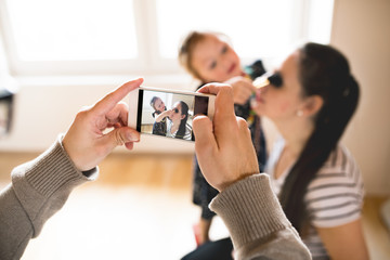 Man taking picture with smartphone of his wife and their daughte
