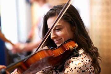 Young female college student playing violin in recording studio