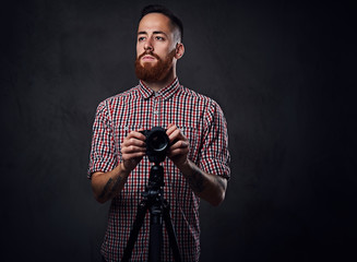 A man holds digital camera and a tripod.