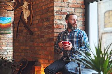 Portrait of bearded male dressed in a blue fleece shirt, drinks hot coffee.