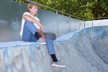 Portrait of a teenager sitting in front of a wall of graffiti with a skateboard