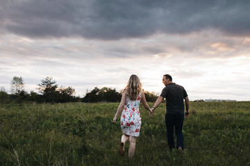 Rear view of romantic couple holding hands in field
