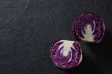 Halved red cabbage on black background