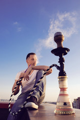 man smoking hookah on the roof of building in sunset