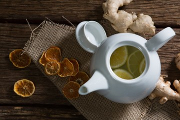 Lemon slice in teapot with ginger and dried orange on wooden