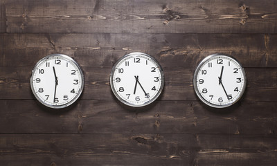 Three wall clocks on different time zones