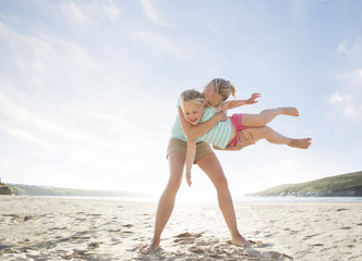 Mother and Daughter having fun on the beach in the summertime.