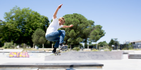 Skater jumps high in air on background blue sky