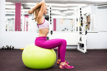 Woman in gym sitting on exercise ball using weights