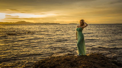 A beautiful sexy blonde in a long turquoise dress stands on the seashore against a backdrop of a bright sunset