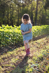 Young girl walking on farm, holding hands together