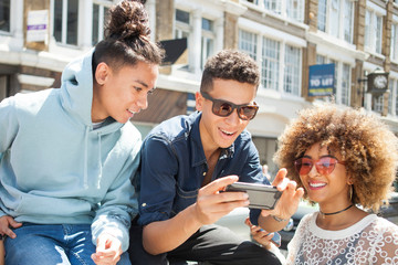 Young friends watching smartphone outdoors