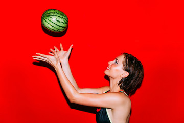 Woman throwing and catching a watermelon