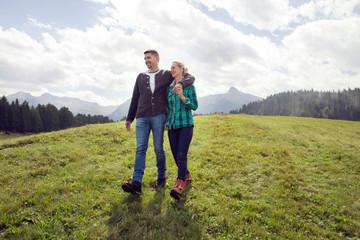 Couple walking in field, Tirol, Steiermark, Austria, Europe
