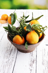 Tangerines with leaves on wooden background. Mandarins Rustic