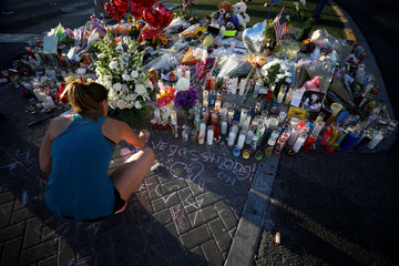 A woman draws with chalk at a makeshift memorial in the middle of Las Vegas Boulevard following the mass shooting in Las Vegas