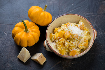 Risotto with pumpkin served in a bowl on a dark brown stone surface, studio shot