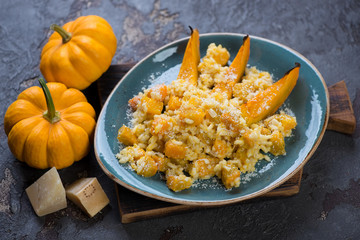 Turquoise plate with pumpkin risotto on a wooden serving board, studio shot