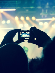 Concert crowd filming a live stage