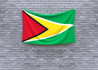 Guyana flag hanging on brick wall. 3D illustration