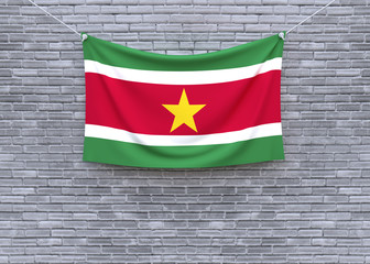 Suriname flag hanging on brick wall. 3D illustration