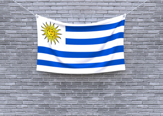 Uruguay flag hanging on brick wall. 3D illustration