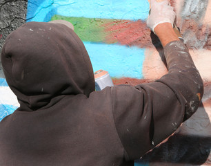 writer with dirty sweatshirt while painting a mural