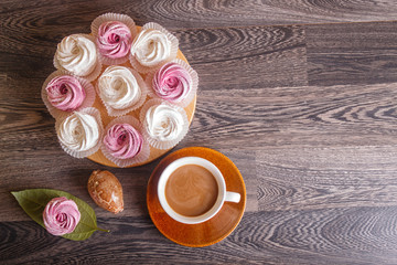 pink and white marshmallows (zephyr) with cup of coffee on a gray wooden background