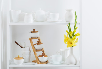 white dishvare with flowers on wooden shelf