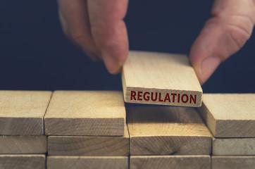 Regulation word written on wooden block.