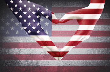 Hands of a young man forming a heart patterned with an American flag