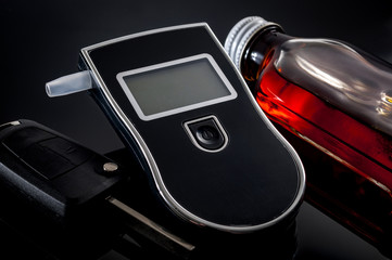 DUI and Don't drink and drive concept with a breathalyzer next to a bottle of alcohol and the car keys. A breath alcohol analyzer can be used to test if a person is capable of driving or not