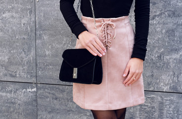 Trendy girl outfit wear pink suede skirt with black little bag