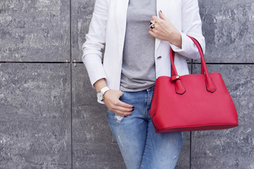 Wall Mural - Casual woman in white jacket with red bag in hand street look