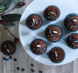 Mini Frosted Chocolate cupcakes on Christmas Holiday background